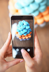 Female hands making photo of varicolored macaroons with mobile phone