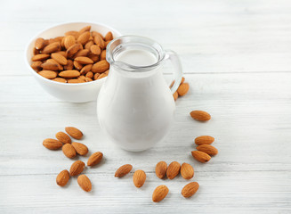 Jug of milk and almond nuts on table