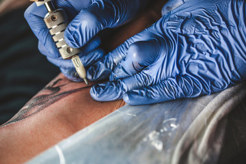 master tattooist does the tattoo in gloves on the hand of the man