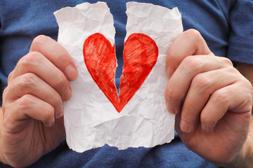 Young man ripping red heart on a piece of paper.