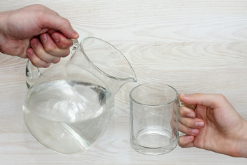 need for clean water/hand with a jug of water and hand with empty glass