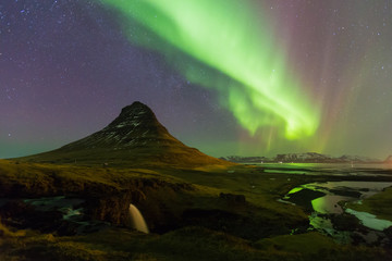 Northern lights over Kirkjufell volcano with fully of stars over the sky