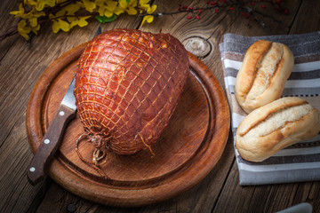 Whole ham on a wooden table.