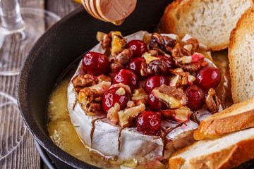 Homemade baked brie with honey, cranberry and walnut.