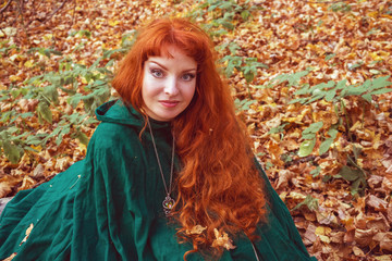 A fairytale fantasy. Red-headed woman in autumn forest. She dressed in renaissance costume.