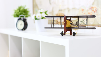 toy wooden airplane is on shelf at home