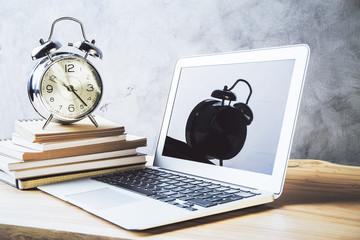 Laptop, alarm and books