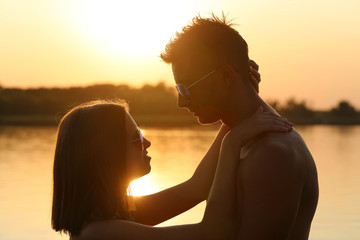 Silhouette of young couple looking at each other at lake