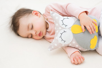 Adorable close-up portrait of sleeping and dreaming baby toddler girl with an owl toy