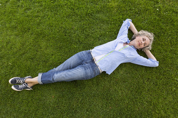 Middle-aged woman in casual weekend clothing relaxing on the grass in a park. She is smiling with a happy, contented expression and looks like she is daydreaming.