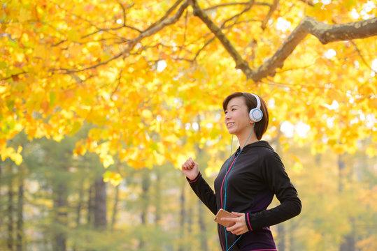スマートフォンで音楽を聞きながら歩く女性