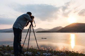 yound man taking camera at dam in the evening