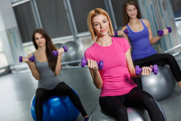 Young women with beautiful shapes and flowing hair, dressed in sports clothes,carry out a workout in the fitness center,performing exercises with dumbbells for arm muscles,sitting on gymnastic ball