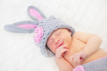 Sleeping smiling newborn baby as rabbit