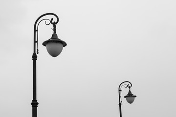 two street lamps on cloudy sky background