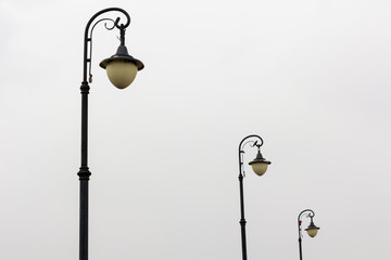 three street lamps on cloudy sky background