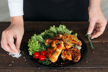Wall Mural - Top view of food decoration on wooden table. Chief presents grilled spicy chicken. Decorating chicken wings with lettuce and tomatoes cherry.