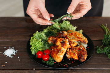 Wall Mural - Food decoration on wooden table. Chief presents grilled spicy chicken. Decorating chicken wings with lettuce and tomatoes cherry.
