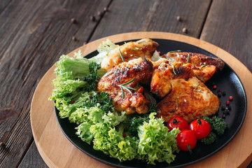 Wall Mural - Grilled chicken wings with fresh vegetables. Baked chicken meat with lettuce and tomatoes cherry. Homemade meat on wooden table.