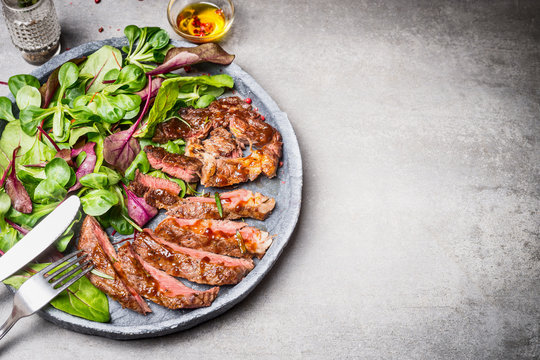 Sliced grilled beef steak with green leaves salad on rustic plate with cutlery. Medium rare barbecue steak and healthy salad on gray stone background, top view, place for text