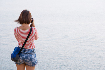 Woman taking photos with smartphone at Railay Beach, Krabi, Thailand.