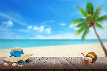 Hat, sunglasses, coconut, shell on beach table. Free space for text. Beach, sea, palm and blue sky in background.