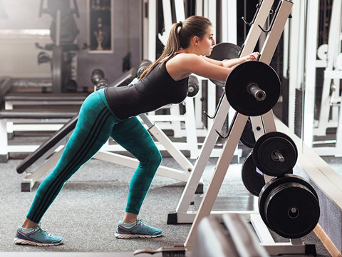 Professional young weightlifter prepares to lift barbell in gym interior. Strong woman weightlifter stay near the barbell in gym, there are legs exercise.