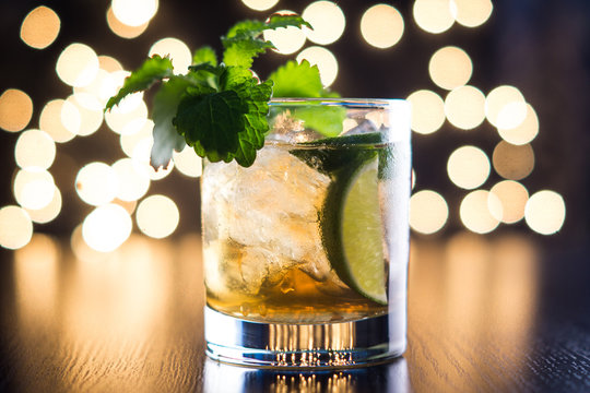 Old fashioned cocktail with lime and mint on the wooden table
