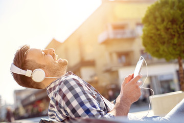 Young man listening to music on a smart phone