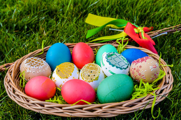 Easter eggs - Easter painted eggs in basket on grass - symbol of Easter