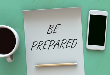 BE PREPARED, message on paper, smart phone and coffee on table