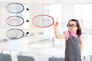 Cute little girl wearing business dress and drawing diagram on whiteboard. Office background.