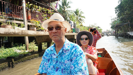 Asian senior couple travel to thailand cruising on the boat in f