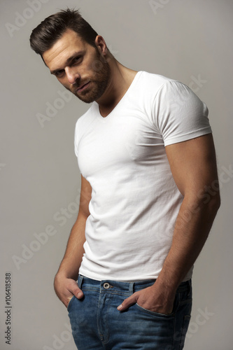 quothandsome young man in white t shirt and jeans on gray