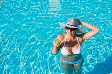 Joyful woman having fun bathing in hotel resort spa pool and drinking cocktail on summer vacation.