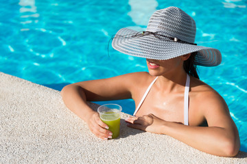Elegant woman wearing fashion sun hat and drinking cocktail while bathing in hotel resort spa pool on summer vacation.