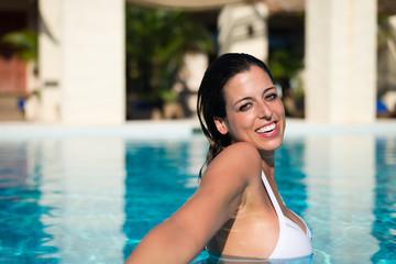Happy woman having fun in hotel resort spa pool on summer vacation.