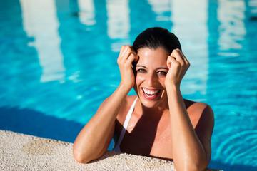Joyful natural woman having fun in hotel resort spa pool on summer vacation.