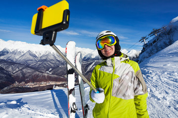 Smiling skier woman take selfie with stick