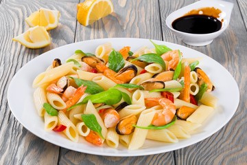 penne pasta salad with shrimps, mussels and baby spinach
