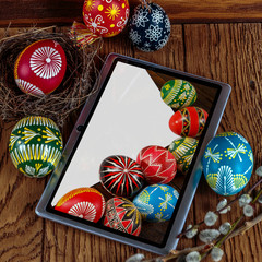 Easter eggs, branches of blossoming willow, a tabled pc on the wodden background