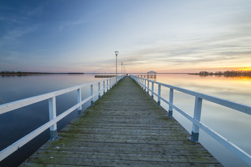 wooden, white pier on the bay at sunset