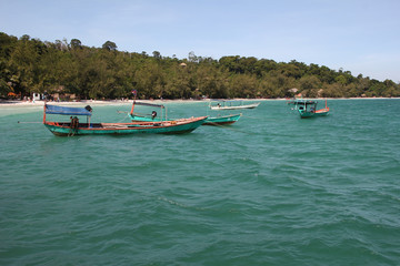 Trip wooden boats in pristine turquoise water near tropical island.