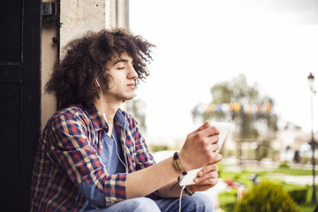 Young man listening music with digital tablet