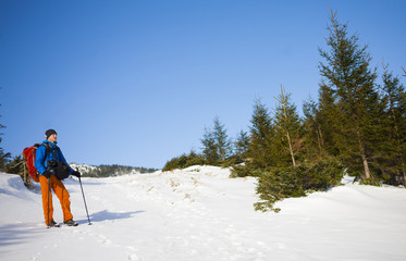 The climber goes on the snow slope.