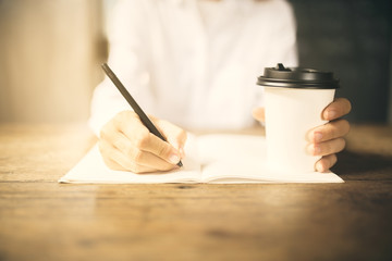 Girl writes in a diary with cup of coffee