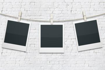 Polaroids on white brick