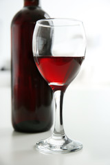 Glass of red wine with bottle on blurred interior background