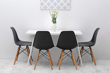 Modern dining room. White table with bouquet of flowers and black chairs, abstract picture on the wall