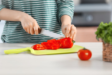 Young woman cutting vegetables for salad in the kitchen
